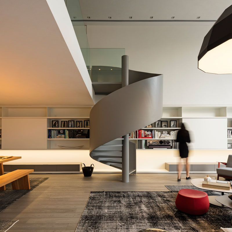 This modern house has grey spiral stairs that lead up to a mezzanine. #SpiralStairs #Stairs #GreyStairs