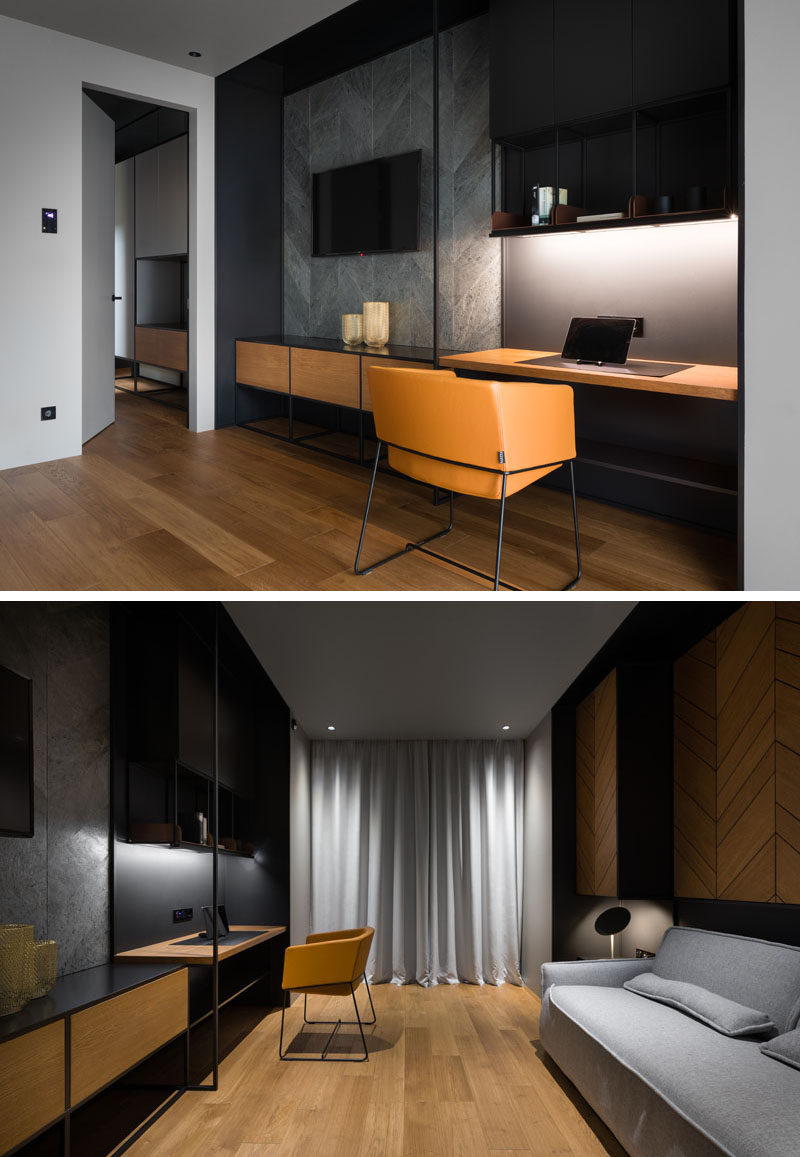 In this modern home office / guest room, there's a wall with a storage cabinet below the television, and beside it, a work area with upper storage cabinets and display shelves. #HomeOffice #GuestRoom