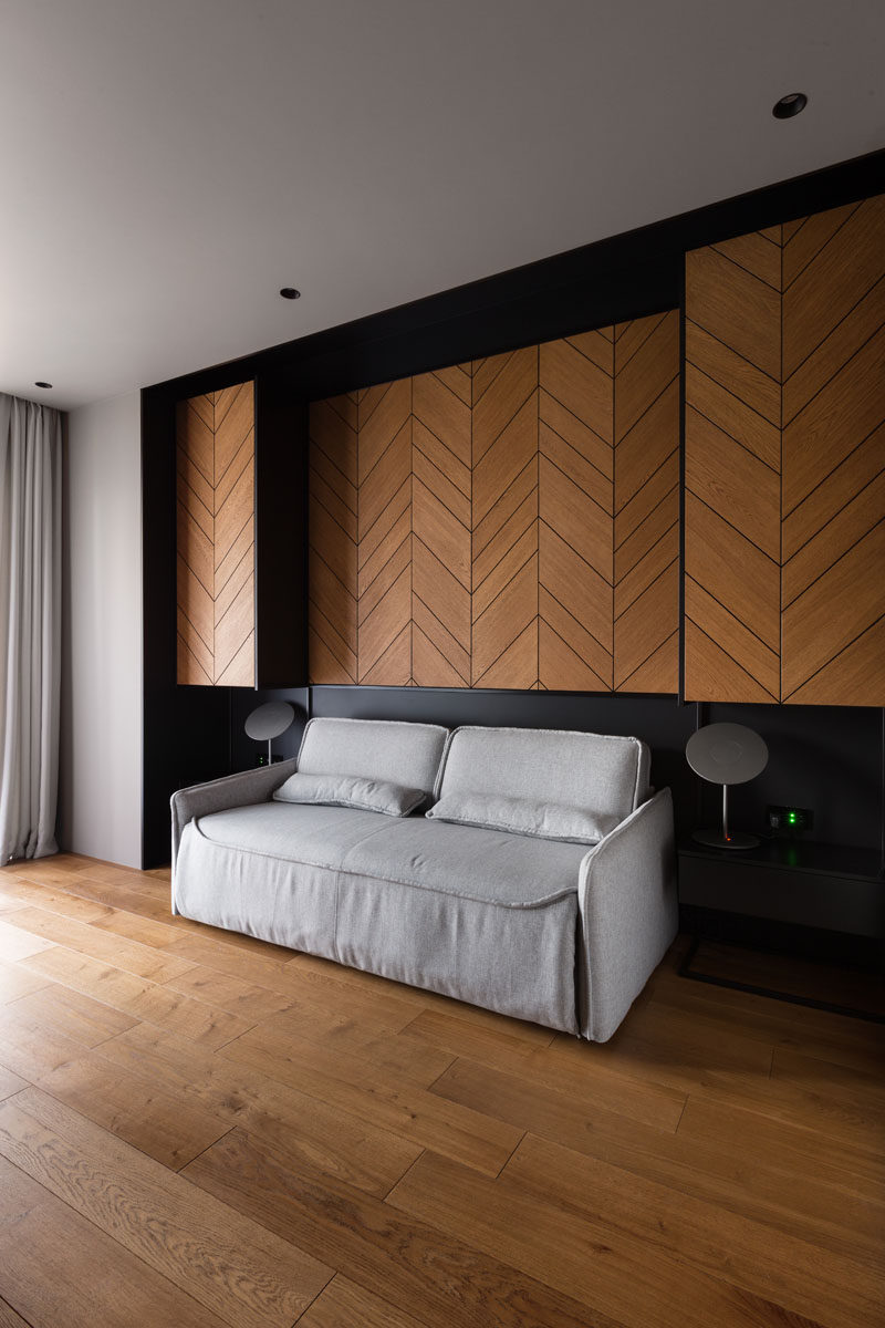 In this home office / guest suite, there's a wood accent wall with a chevron pattern. A couch sits between two side tables, and when required for guests, can be transformed into a bed. #HomeOffice #GuestSuite #ChevronAccentWall