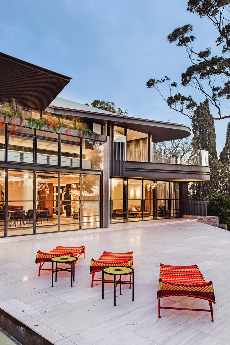 This modern house opens up to a large backyard, with a terrace connecting the house to the swimming pool and cabana. #ModernHouse #HouseDesign #Landscaping