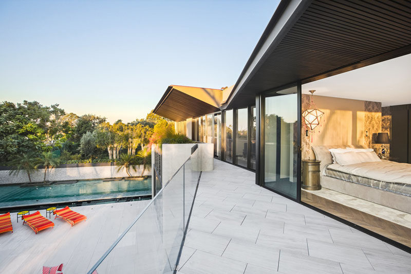 The bedrooms located on the upper floor of this modern house, open to a balcony that has a view of the backyard and swimming pool. #Balcony #ModernHouse