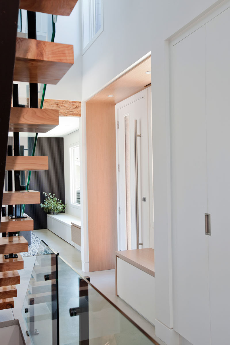 Inside this modern house, the entryway is lined in wood with a built-in bench beside the front door. #FrontDoor #Entryway