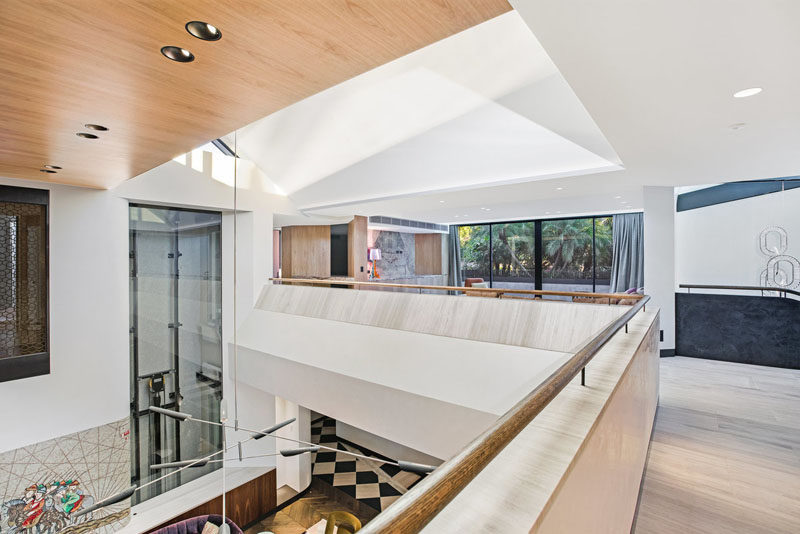 This modern house has a central double volume atrium, that overlooks the living room below and is lit by upper-level skylights. #ModernHouseDesign #Atrium