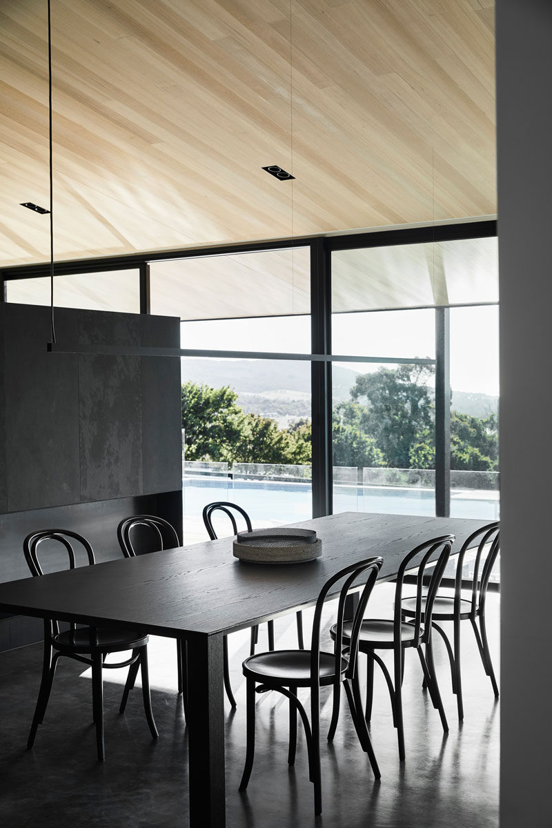 This modern farm house features light oak wood ceilings and large windows that show off the views and the swimming pool from the dining room. #WoodCeiling #DiningRoom