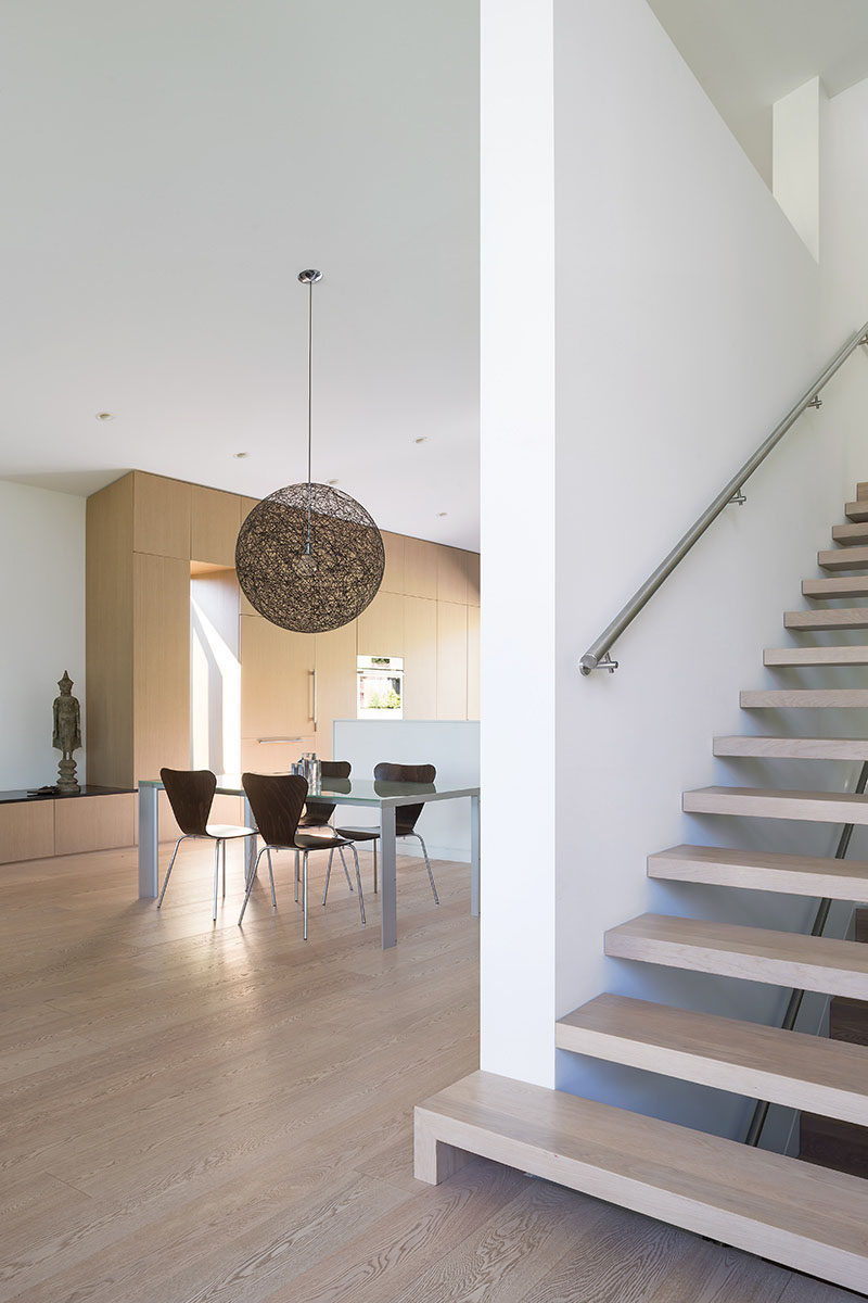 Wood stairs lead up from the main floor of this modern house, to the partial third storey that contains a new office, and a master bedroom and ensuite. #Stairs #ModernInteriorDesign #WoodStairs