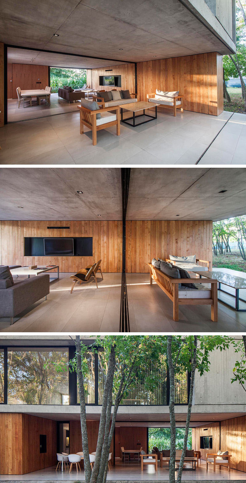 The interior concrete ceiling and wood wall of this modern house, extends to provide shade and protection for the outdoor living room and alfresco dining area. #Architecture #InteriorDesign #WoodWall #ModernHouse