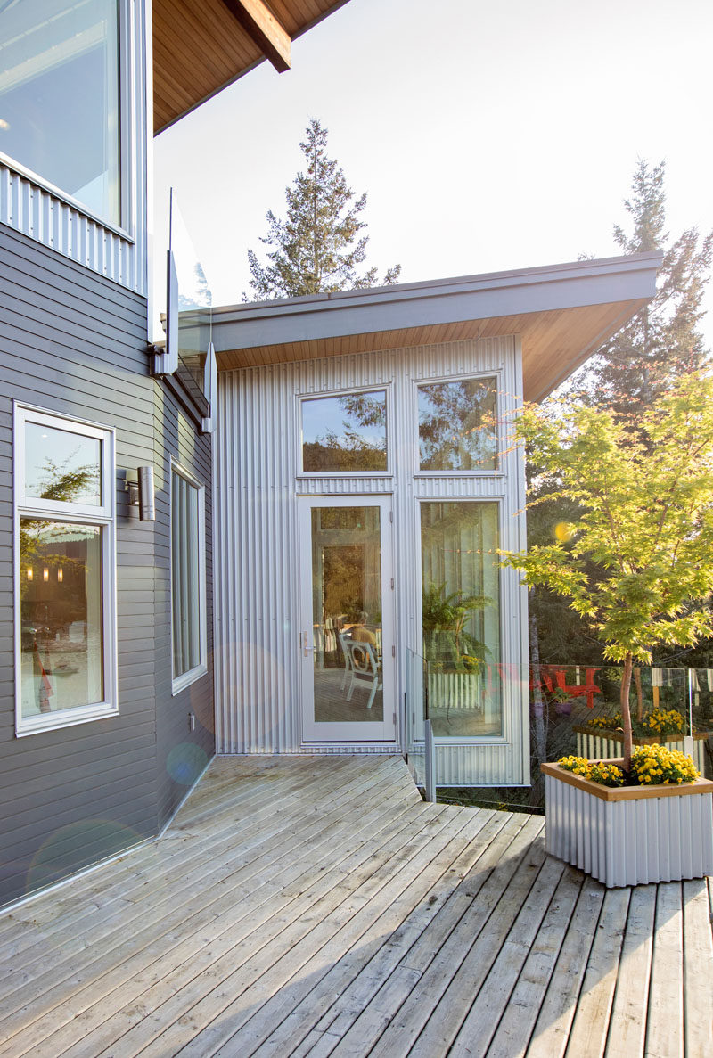 This modern house uses dark blue horizontal siding and silver corrugated vertical siding. #ModernHouse #HouseSiding