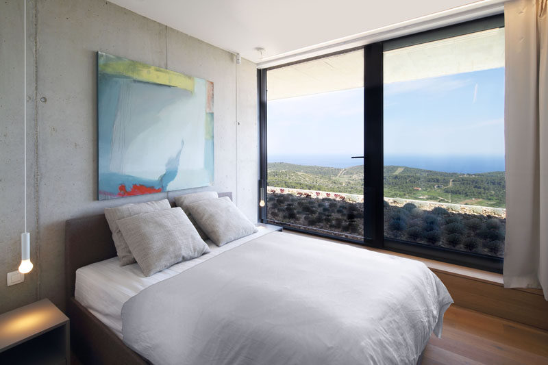 This bedroom has large windows that take advantage of the water views, and provide a glimpse of the green roof. #BedroomDesign #Windows