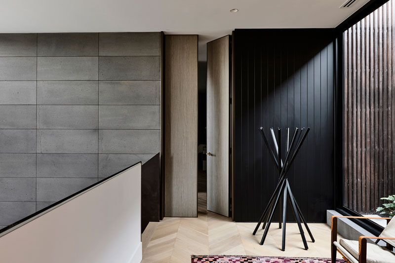At the top of the stairs in this modern house, wood doors open to reveal the bedrooms, while large windows provide a glimpse of the garden outside. #ModernInteriorDeisgn
