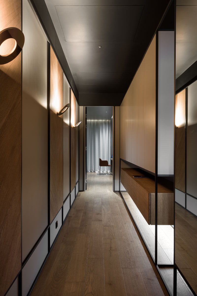 Hallways with wood panels highlighted by scones lead to the more private areas of this modern home, like the home office / guest room, and the bedrooms. #Hallway #ModernSconce