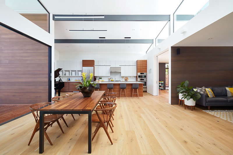The dining table is central to the open interior of this modern house, and the clerestory windows that meet the high sloping ceiling help to make the space light and airy. #ModernDining #Windows #HighCeiling
