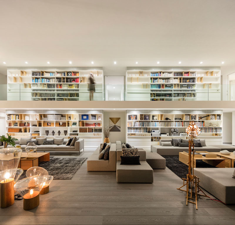 This modern living room features multiple seating areas, a double height ceiling, and a large bookshelf. #ModernLivingRoom #LivingRoom #Bookshelf #HomeLibrary