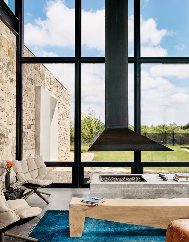 This modern house has large black framed windows that match the black steel fireplace flue. #Fireplace #SteelFireplace #Windows