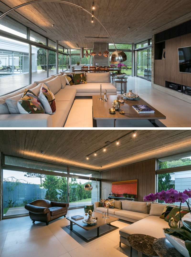 This modern living room features an Italian walnut home theatre and custom design L-shaped lights on the ceiling. #LivingRoom #ConcreteCeiling #Lighting
