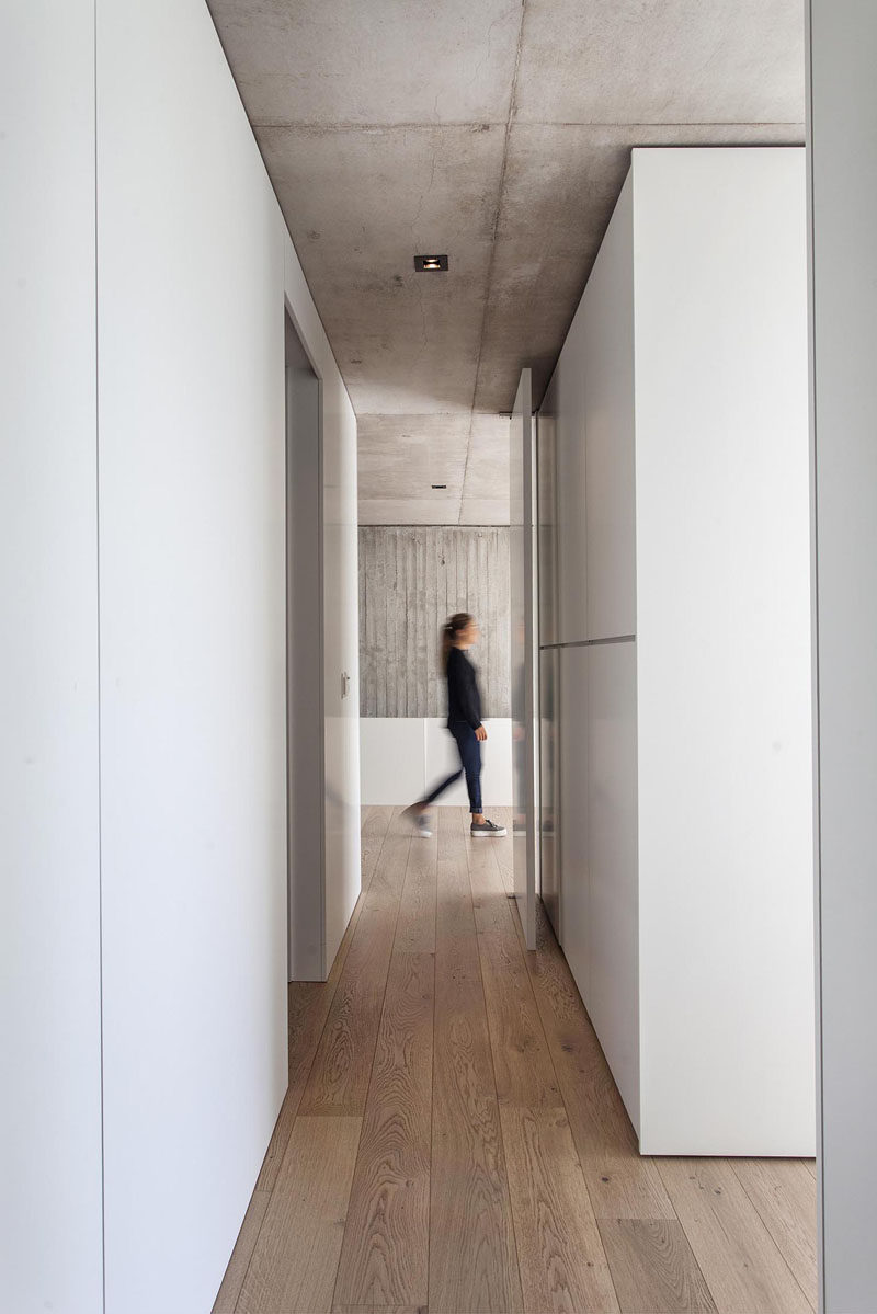 Raw concrete contrasts the bright white walls and cabinets that line the hallway in this modern house, while wood flooring adds warmth and a natural touch. #ConcreteCeiling #WoodFlooring #WhiteHallway