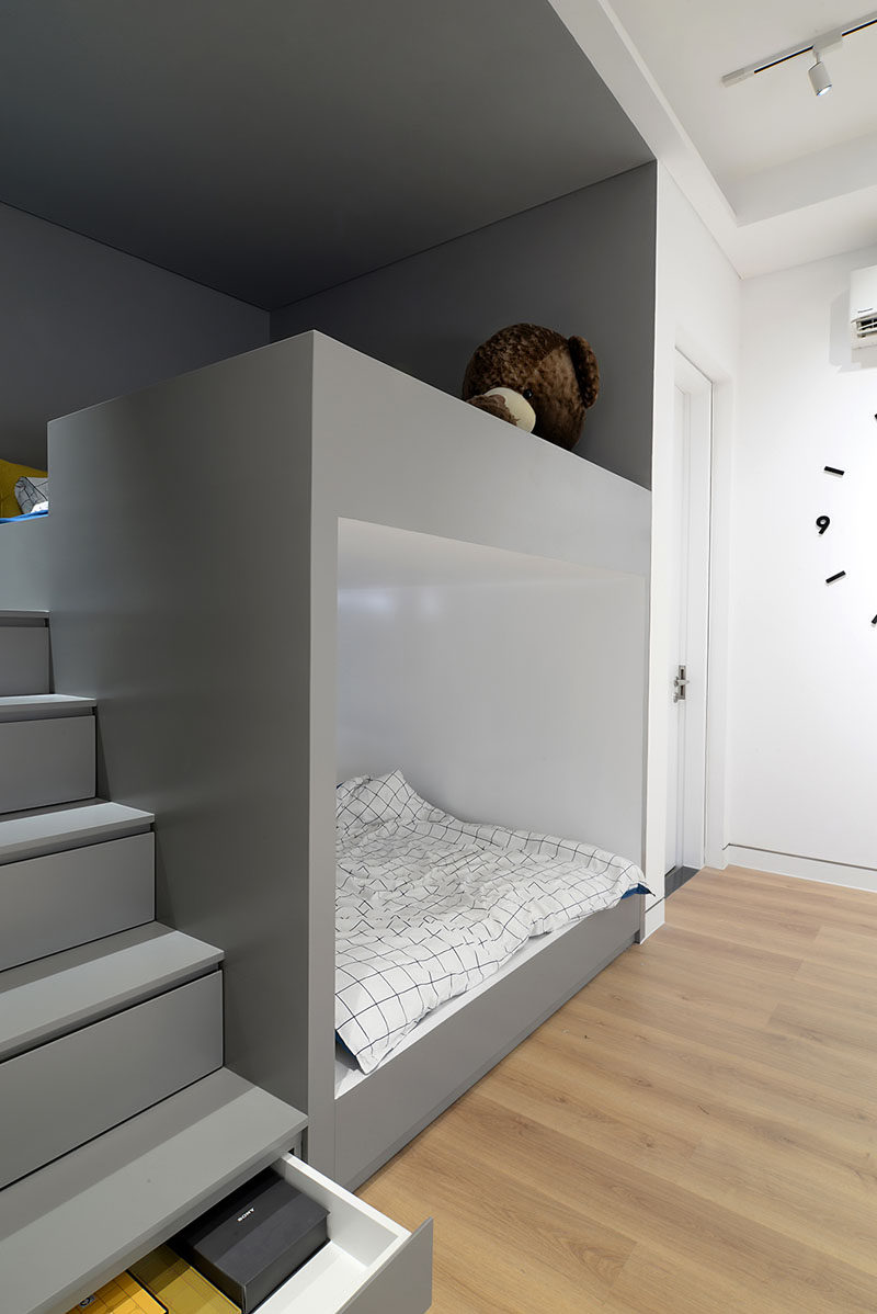 Along One Side Of The Bedroom Is A Grey Alcove That S Home To Built In Bunk Beds With Stairs Leading Top Bed Hidden Within Are Storage