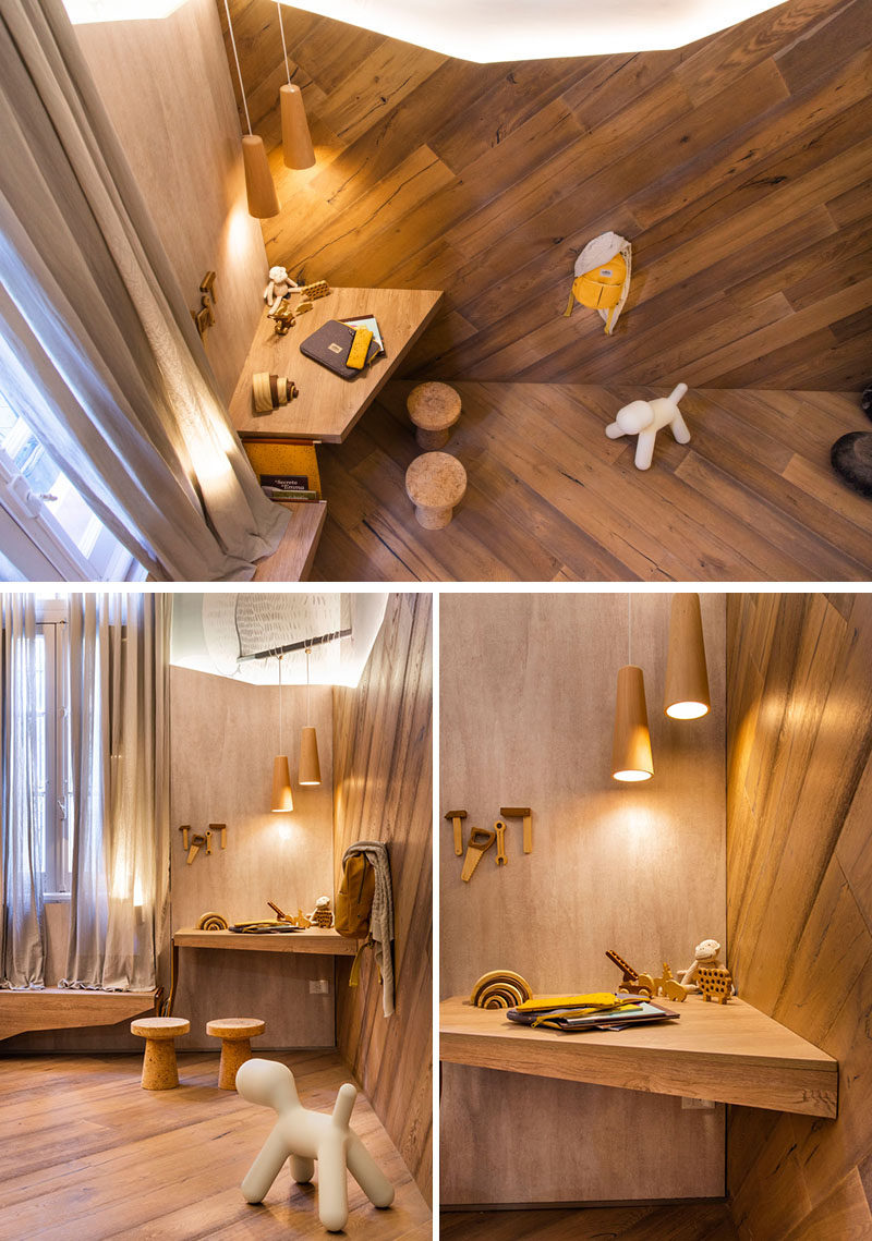 In this modern kids bedroom, diagonal flooring continues up onto the wall, and in the corner, a small angled desk area is positioned beneath two hanging pendant lights. #KidsBedroom #KidsDesk