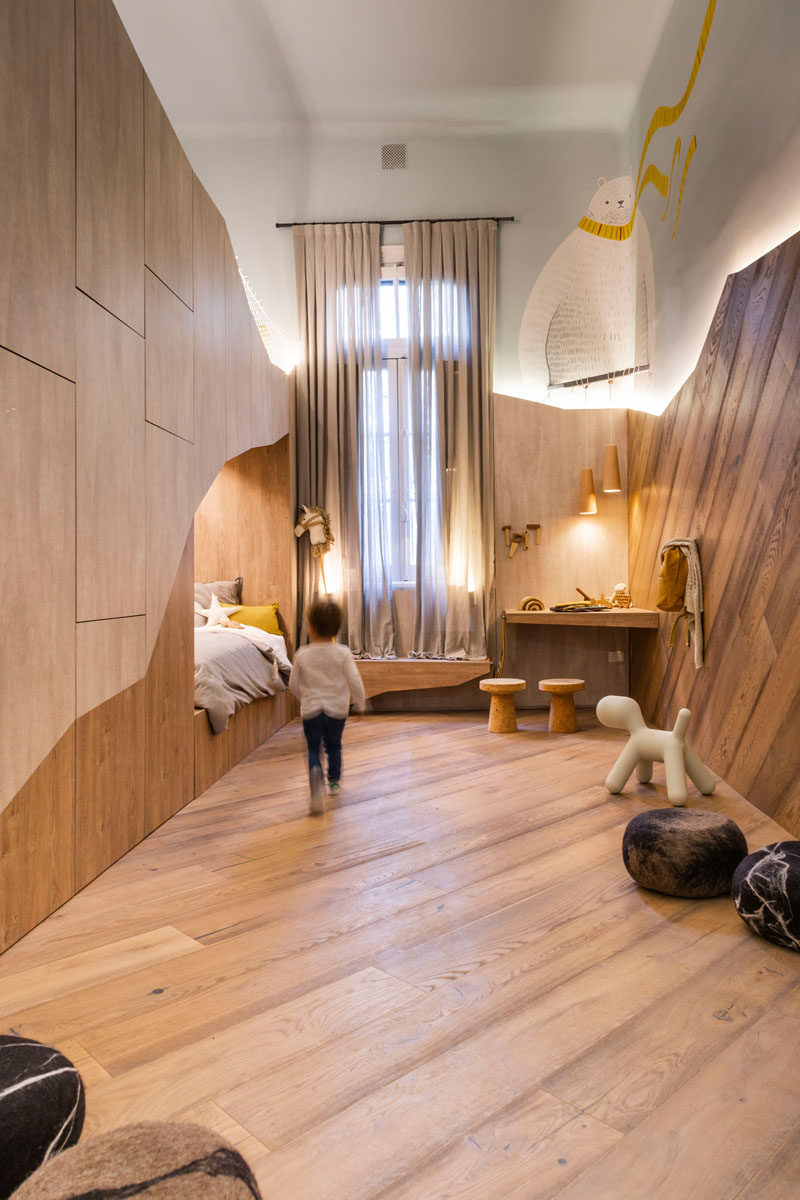 This modern kids bedroom draws inspiration from a bears cave, with the bed tucked away within a 'cave'. #KidsBedroom #InteriorDesign