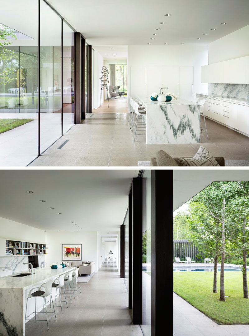 This modern kitchen has a large island, minimalist white cabinets, and floor-to-ceiling windows. Beside the kitchen is a casual den/living room. #WhiteKitchen #ModernKitchen #KitchenDesign