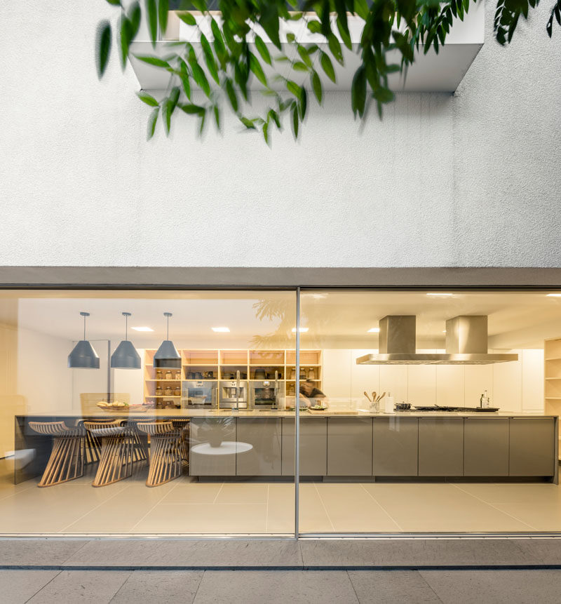 In this modern kitchen, a large island with space for seating is central to the room, while open wood shelving surrounds the wall ovens. #ModernKitchen #KitchenDesign #LargeKitchenIsland