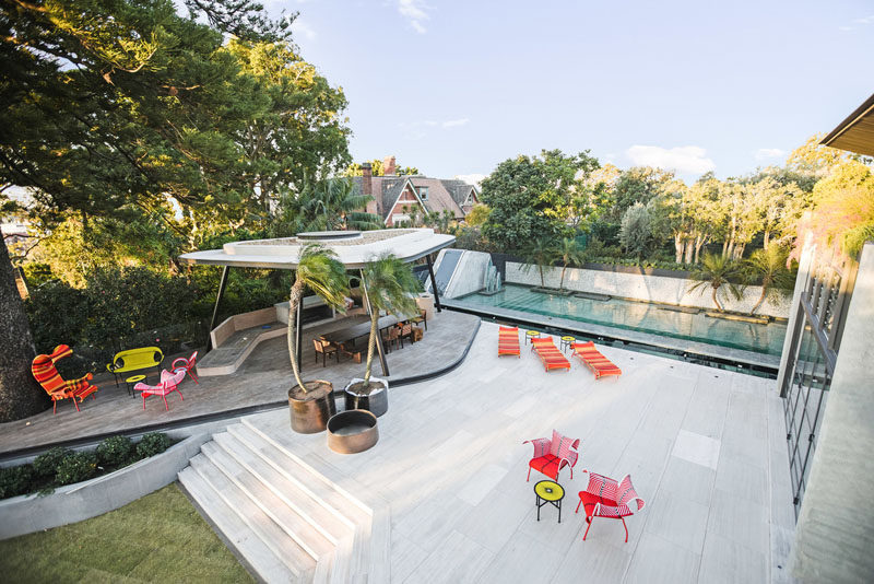 This modern backyard has a large terrace, and a freeform concrete and steel cabana that sits next to a large pool with a 17m glass-bottomed pond feature. #Backyard #Landscaping #Pool #Cabana