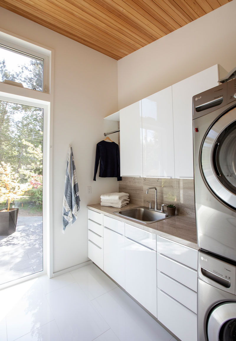 This modern laundry room, with its high ceilings, has plenty of storage in glossy white cabinets, a place to hang clothes and stackable washer/dryer. #ModernLaundry #LaundryRoom
