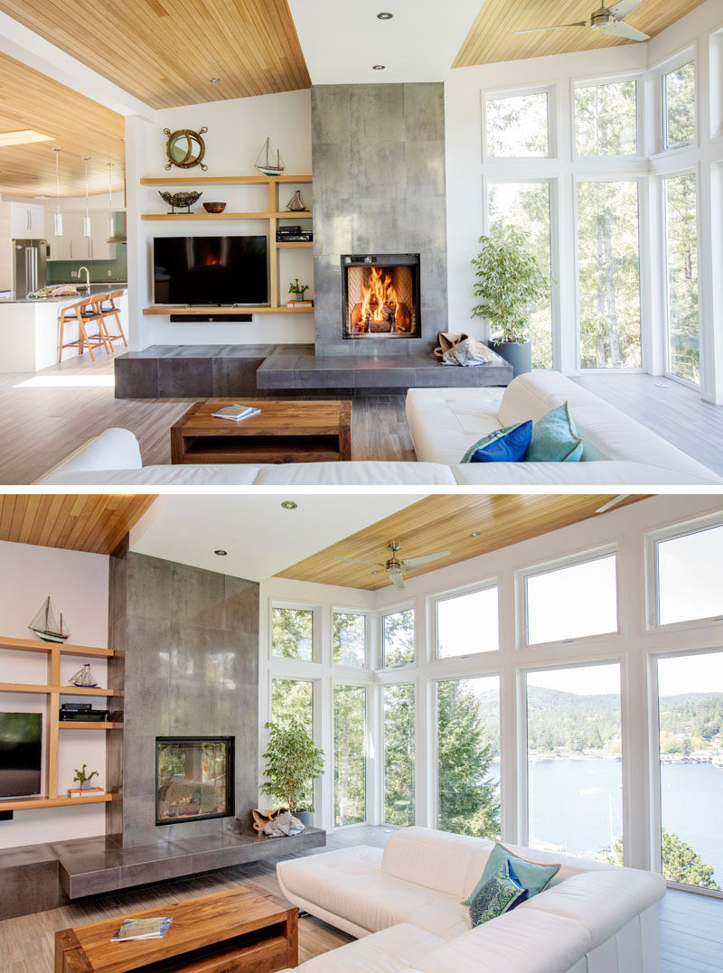 In this modern living room, the fireplace is the focal point, while large windows provide ample natural light and a view of the water. #LivingRoom #Fireplace #Windows