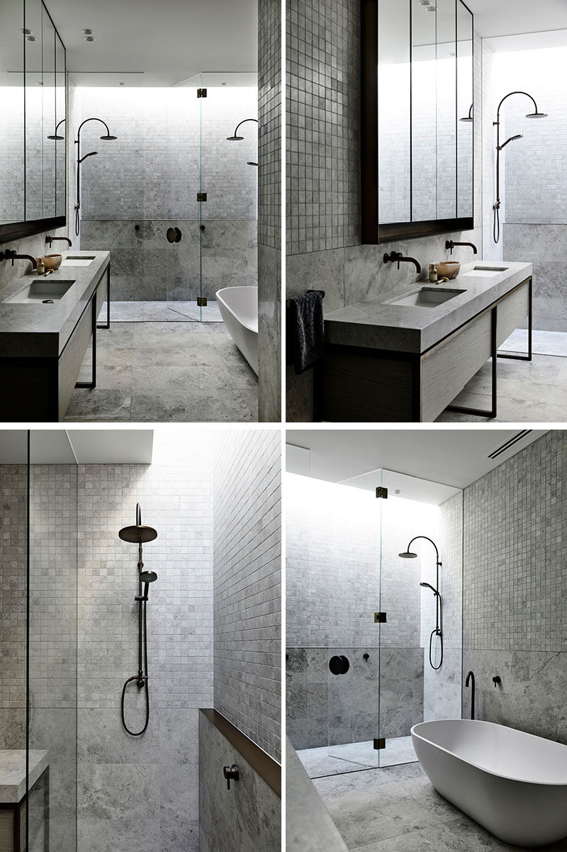 In this modern bathroom, a glass shower screen separates the double-shower from the vanity area and the freestanding bathtub. Grey tiles have been used to create a calming and spa-like environment. #ModernBathroom #BathroomDesign #DoubleShower