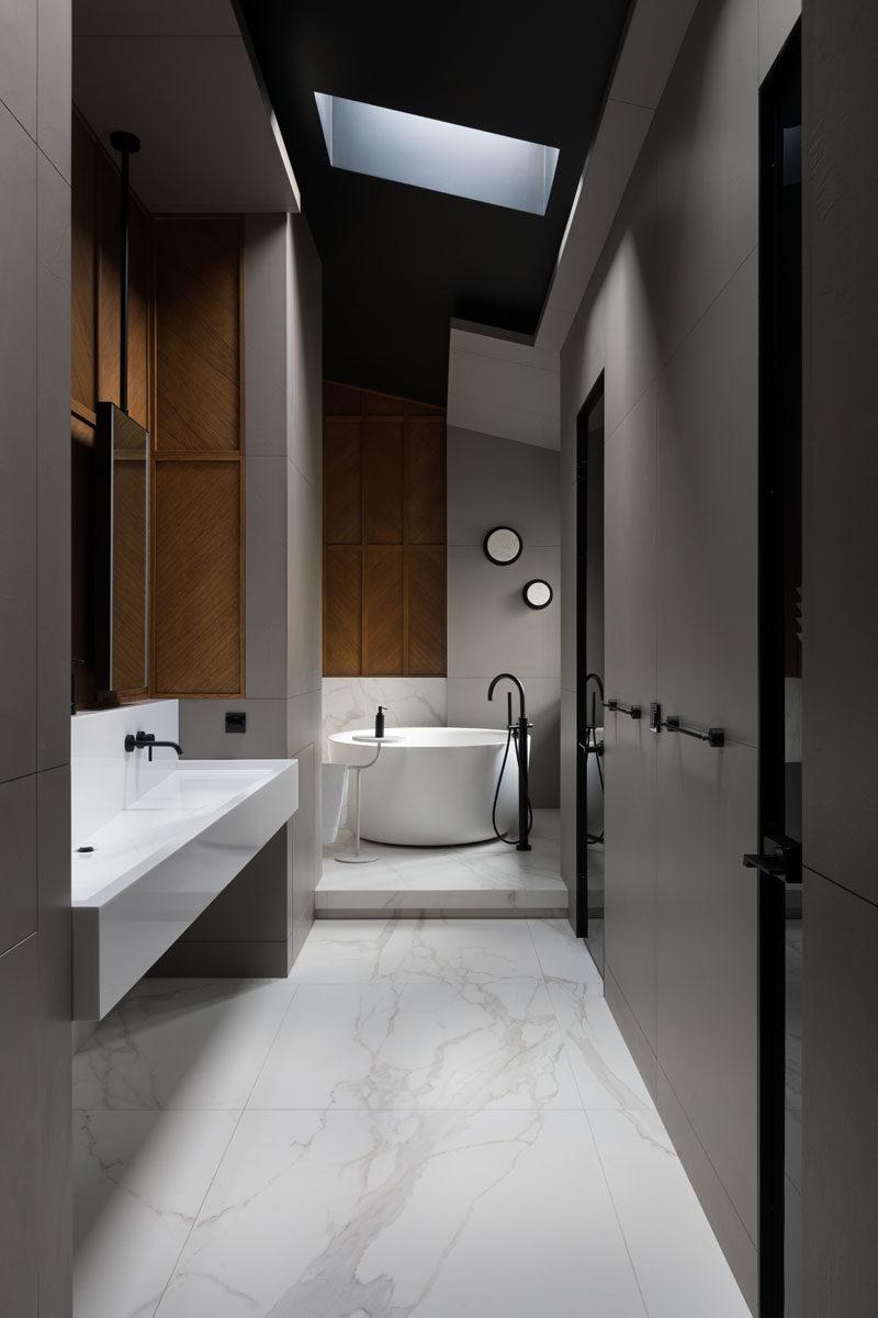 In this modern master bathroom, a round freestanding bathtub has been placed on a raised platform, while a skylight draws the eye upwards to the high ceiling. #MasterBathroom #BathroomDesign #RoundBath