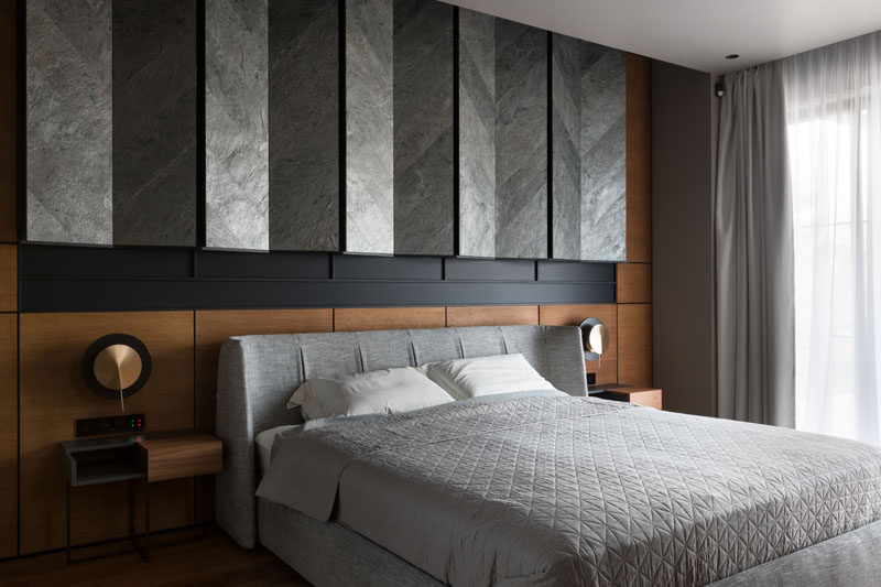 In this modern master bedroom, grey tiles installed in a chevron pattern, have been angled to create a unique wall feature above the bed. #MasterBedroom #BedroomDesign #WallAccent