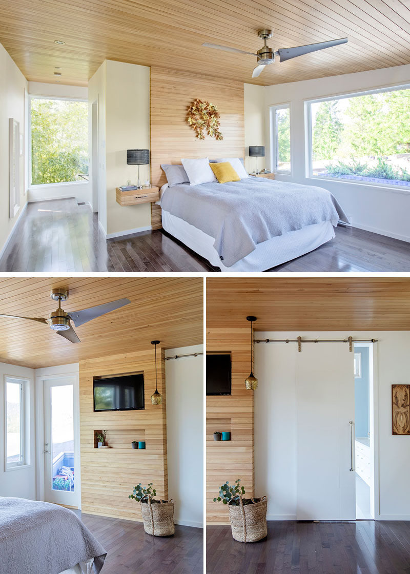 The light wood used on the ceiling of this modern bedroom, has also been used to create an accent wall behind the bed, while wood bedside tables float on either side of the bed. Opposite the bed is a smaller wood accent wall that surrounds a television, and a sliding barn door hides the master bathroom. #ModernMasterBedroom #WoodAccentWall #WoodCeiling