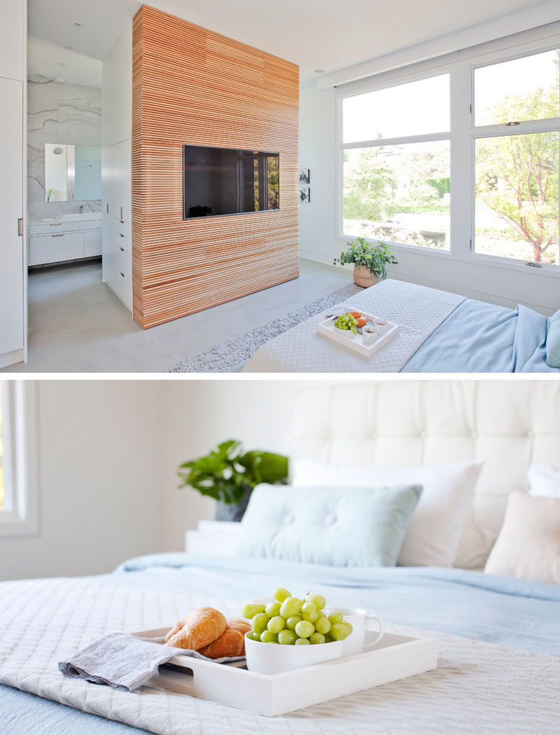 This modern master suite has a wood accent wall that surrounds the television. #WoodAccentWall #BedroomDesign