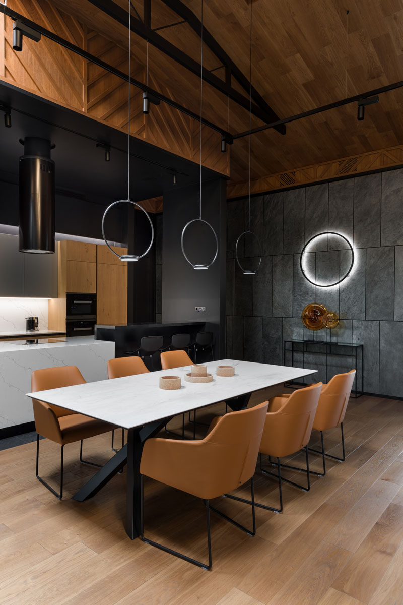 The dining area in this open plan interior, is positioned beneath three minimalist circular pendant lights, separates the living room from the kitchen. #DiningTable #DiningRoom