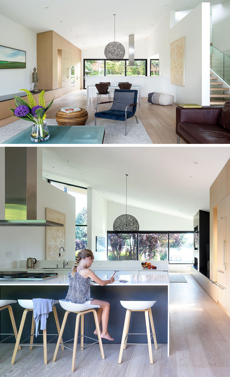 The main floor of this modern house is dedicated to the living room and dining room, and located behind a pony wall is the kitchen, that looks out towards the backyard, however it can also see through to the street at the front of the house. #OpenPlanInterior #PonyWall #InteriorDesign #ModernInterior