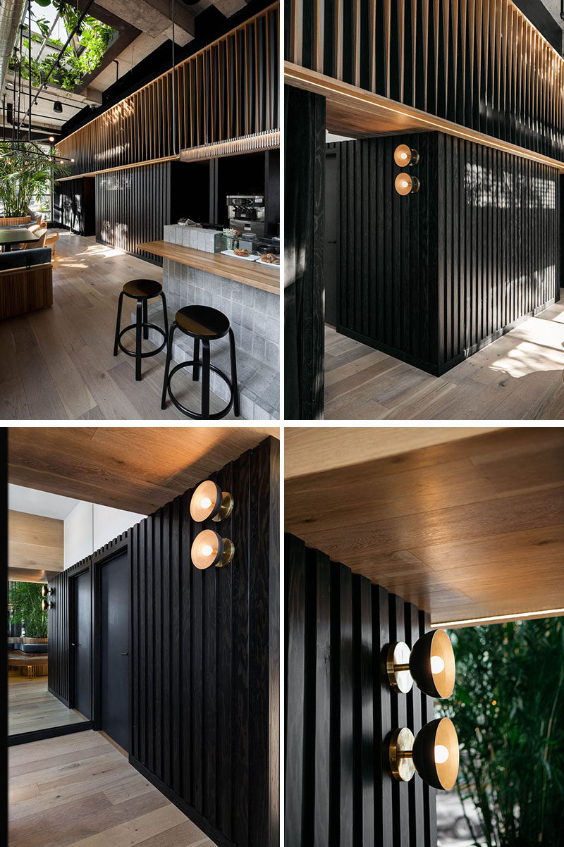 Along the back wall of this modern restaurant, dark and light wood slats create an optical effect that gives movement as you pass through the space. #RestaurantDesign #ModernRestaurant #WoodSlats