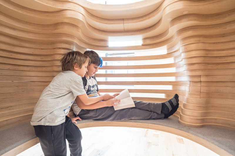 This modern school features custom-designed reading pods made from wood and a felt cushion. #FurnitureDesign #ReadingPod #SchoolDesign