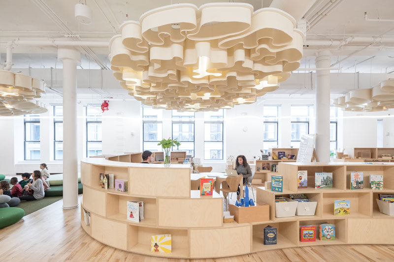 In this modern school, acoustic clouds, hanging from the ceiling and made of felt, reflect the different patterns in nature – fingerprint, coral, landscape and moon – and illuminate with Ketra bulbs that shift in color and intensity based on the time of day. #AcousticClouds #ModernSchool #CurvedShelving