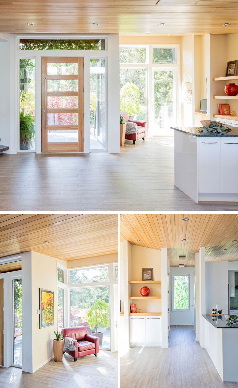 Inside this modern house, there's a small sitting area to the side of the front door, that has a shelving unit, a door to the front sun deck, and doors on either side of the shelf that lead to the laundry and the kitchen pantry. #ModernHouse #Entryway #InteriorDesign