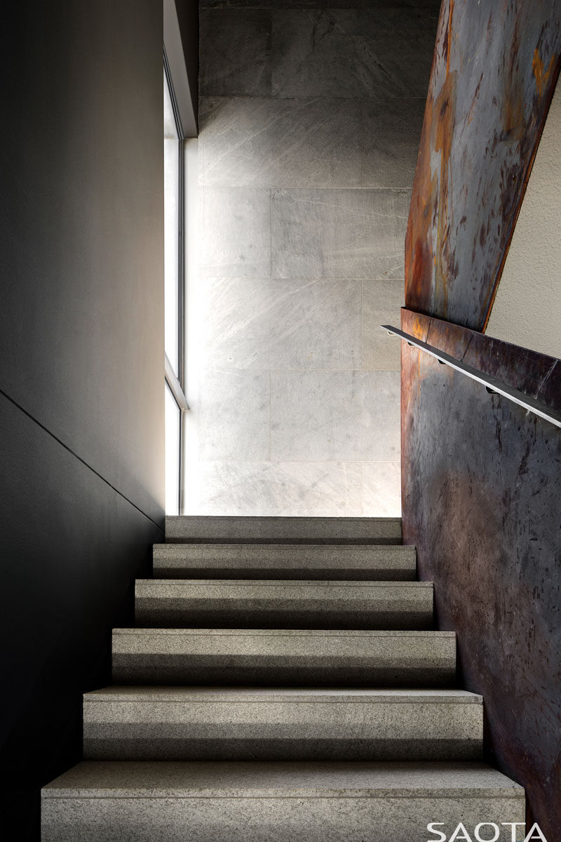 The staircase in this modern house consists of light grey granite stair tiles with crude steel side balustrade sheets that have been left to rust naturally, while the walls are matte silver grey granite. #ModernStairs #SteelBalustrade