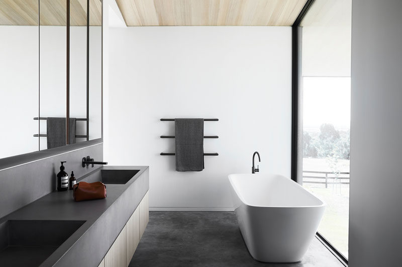 This modern bathroom has a dark grey vanity that features a built-in sink, and a white freestanding bathtub, that's positioned in front of the large floor-to-ceiling window. #Modernbathroom #BathroomDesign