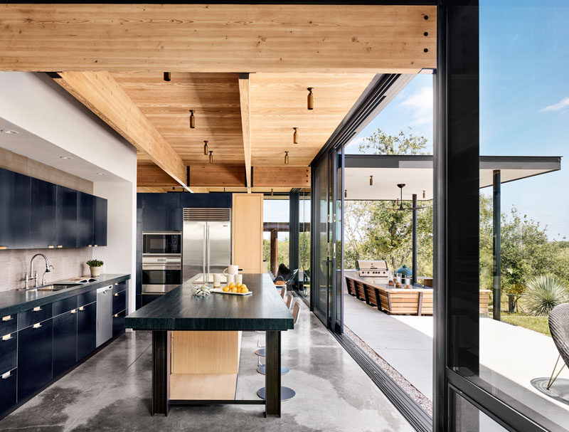 Large sliding glass doors open this modern kitchen with black steel cabinetry, to the patio, where there's a bbq and covered lounge area. #Kitchen #KitchenDesign #ModernKitchen