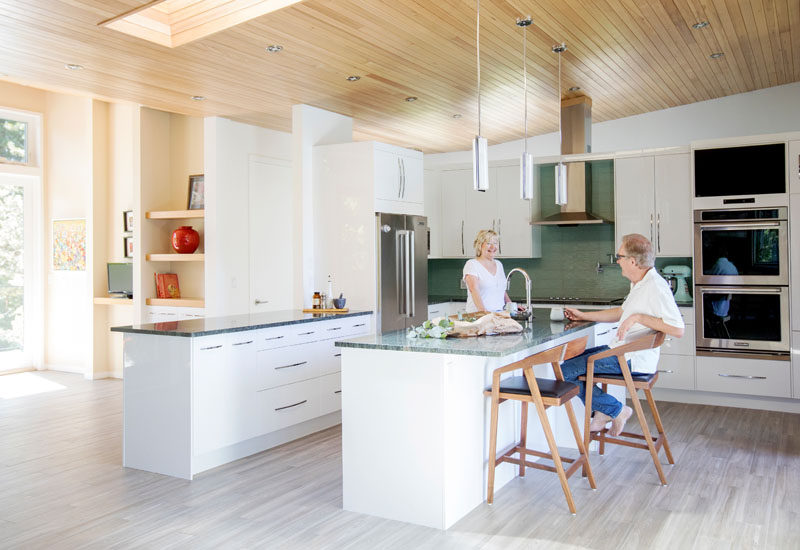 This modern kitchen features white cabinetry and a centrally located island with room for seating. #ModernKitchen #KitchenDesign #WhiteKitchen