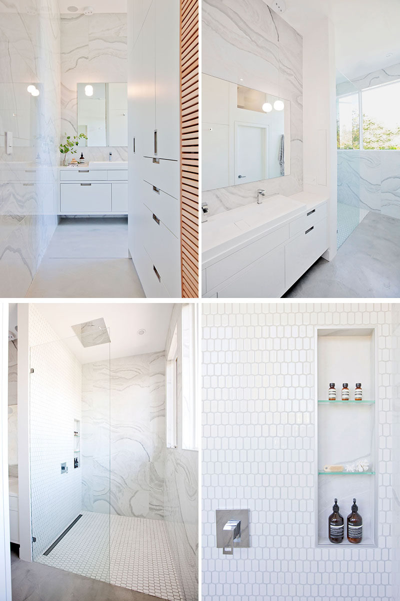 This modern bathroom has been kept bright with the use of light-colored large format tiles and white cabinetry. #ModernBathroom #WhiteBathroom #BathroomDesign