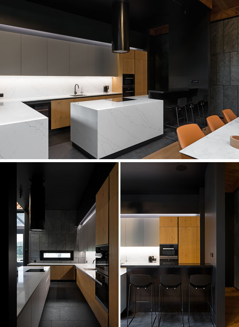 In this kitchen, the minimalist white upper cabinets, countertops, and kitchen island, have been paired with wood cabinetry and a black breakfast bar with seating. #ModernKitchen #KitchenDesign
