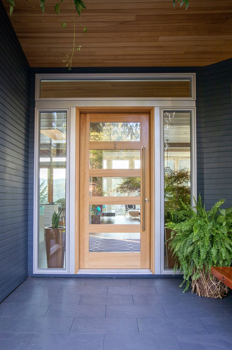 A wood and glass front door surrounded by windows welcomes visitors to the home. #FrontDoor #ModernFrontDoor