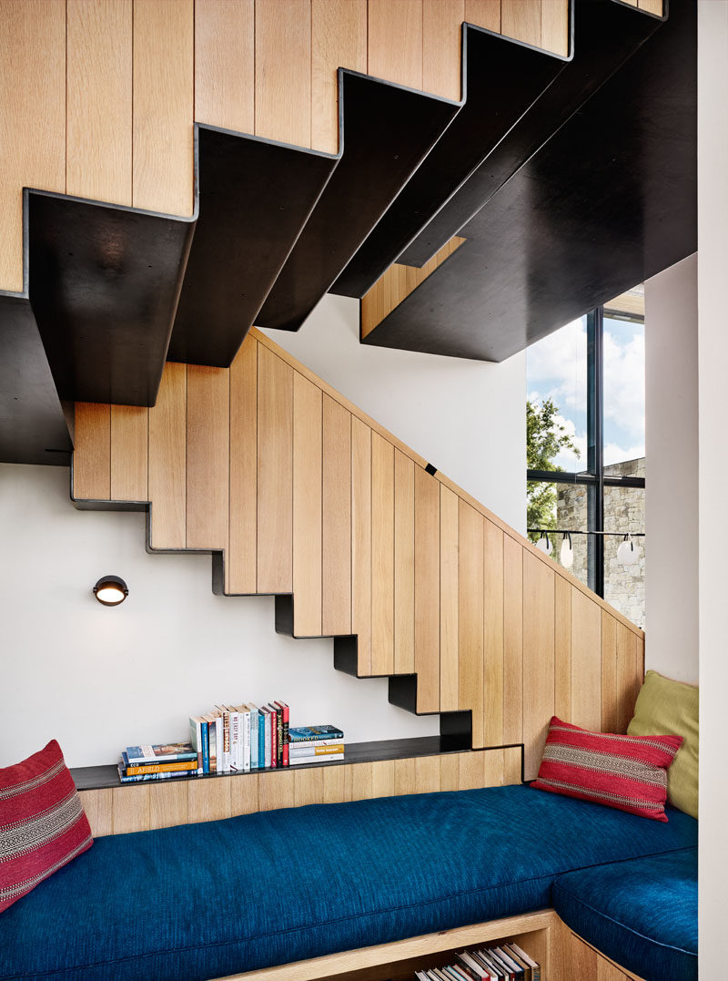 This modern house features steel and wood stairs, and located underneath, a small reading area with blue cushioned benches. #Stairs #StairDesign