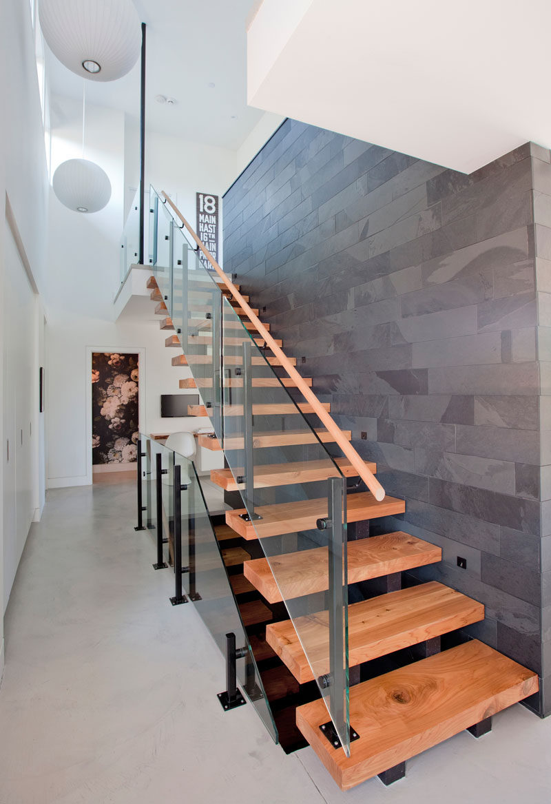This modern house features steel and wood stairs by the front door that lead to the upper and lower levels of the home. #Stairs #ModernStairs #WoodStairs