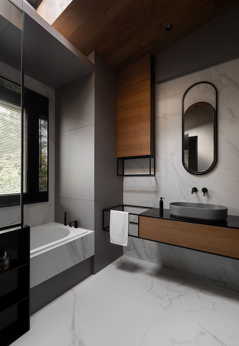 In this modern grey, black, and wood bathroom, curved elements like the mirror and the basin reflect the curved interior shape of the bath. #ModernBathroom #BathroomDesign