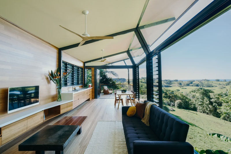 The social areas of this modern guest pavilion are open plan with the living room at one end, the kitchen and dining area in the middle, and a balcony at the other end. #GuestHouse #ModernInteriorDesign