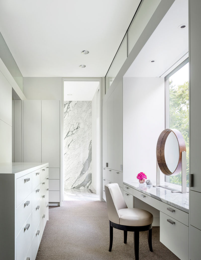 This modern master closet has plenty of storage and a vanity that looks out to the garden. #MasterCloset #ClosetDesign